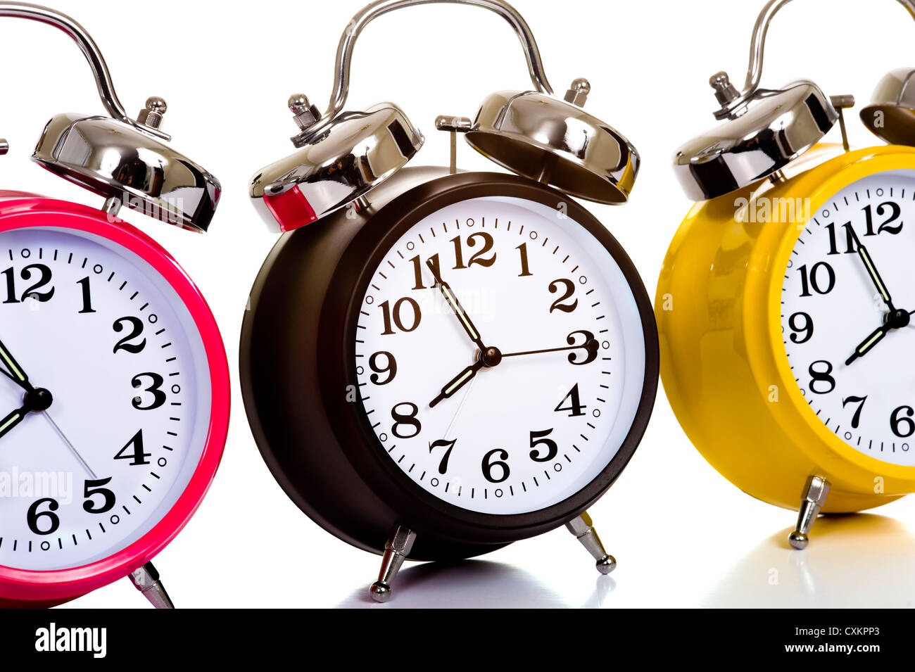 A group of colorful, traditional alarm clocks on a white background, time concept - Stock Image