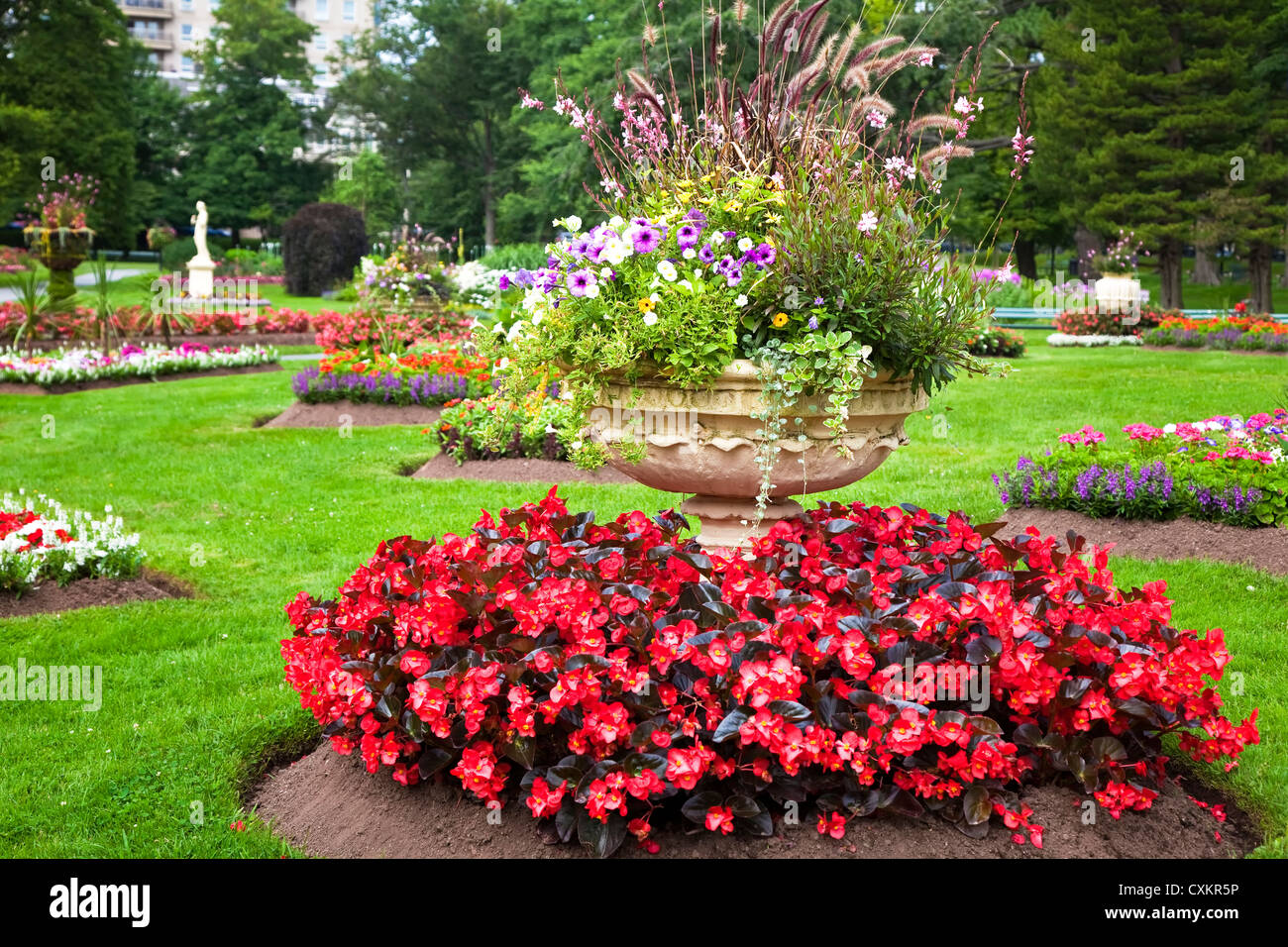Ornate Large Cement Planters Filled With Annual Flowers In The