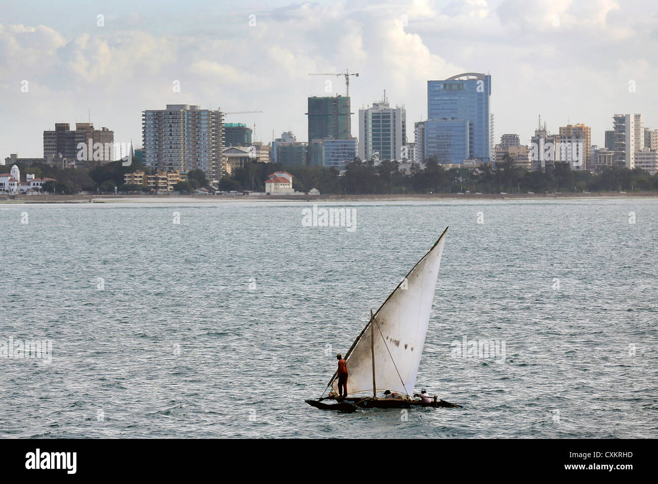 traditional Arab sailing boat (dhow) with Tanzanian capital Dar Es Salaam in the background - Stock Image