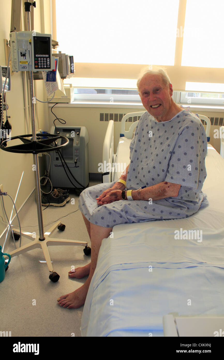 an elderly man in a hospital sitting on a bed in gown after illness treatment or surgery looking at the camera and - Stock Image
