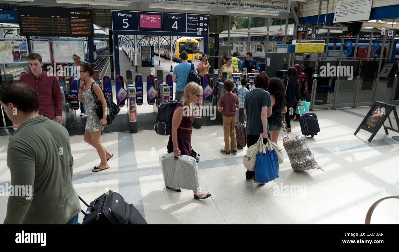 Underground passengers carrying luggage and bags amongst travellers in train station hall at Richmond upon Thames, - Stock Image