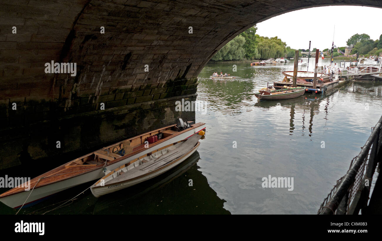 River Thames view of boats and people boating on water seen through bridge tunnel in Richmond upon Thames, London, Stock Photo