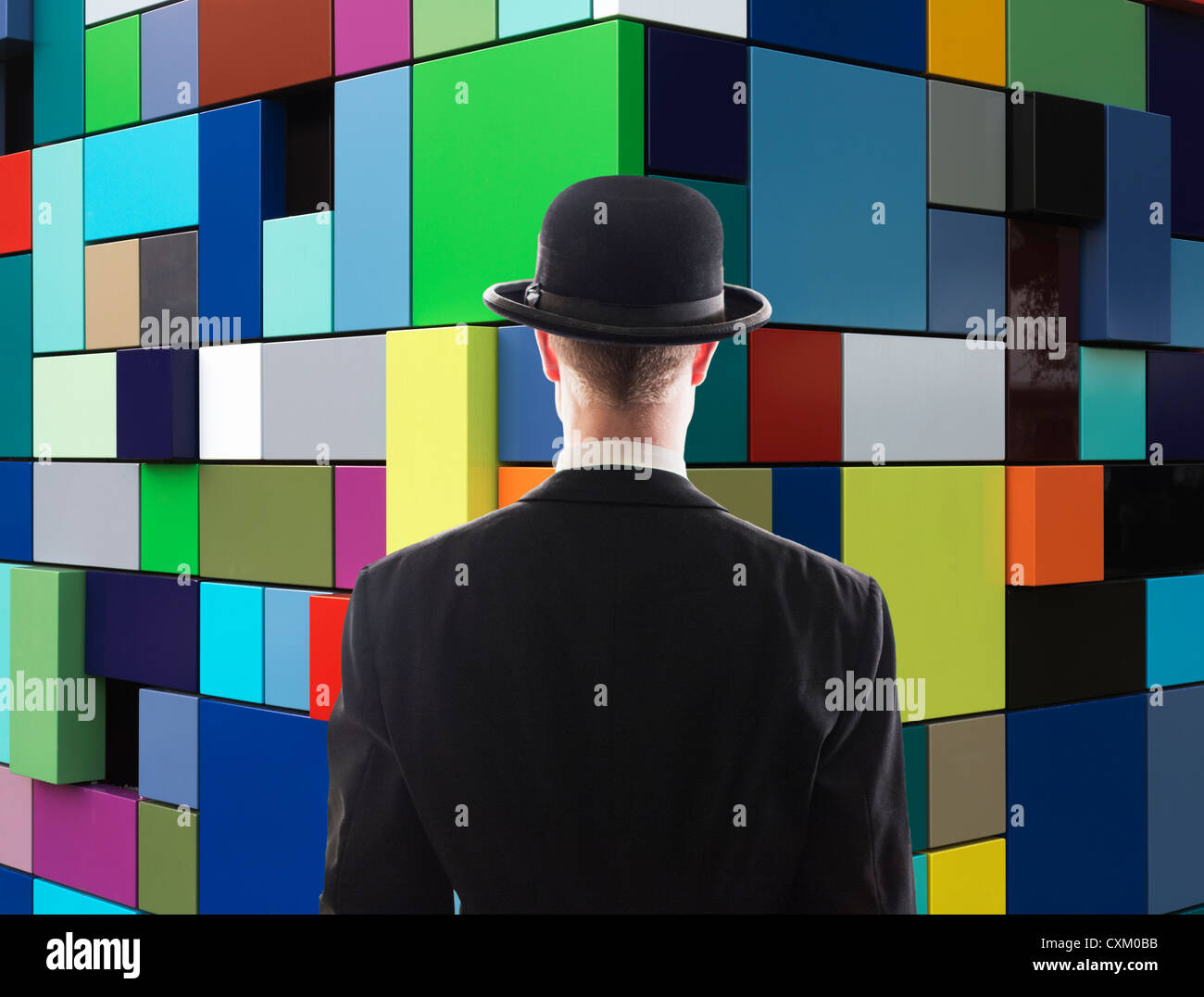 man facing multi-colored wall - Stock Image