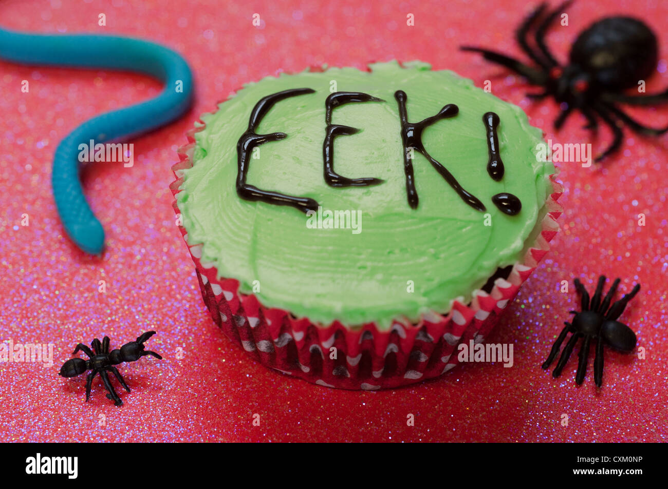 Cupcake with the word eek! iced onto the surface and surrounded by plastic creepy crawlies - Stock Image