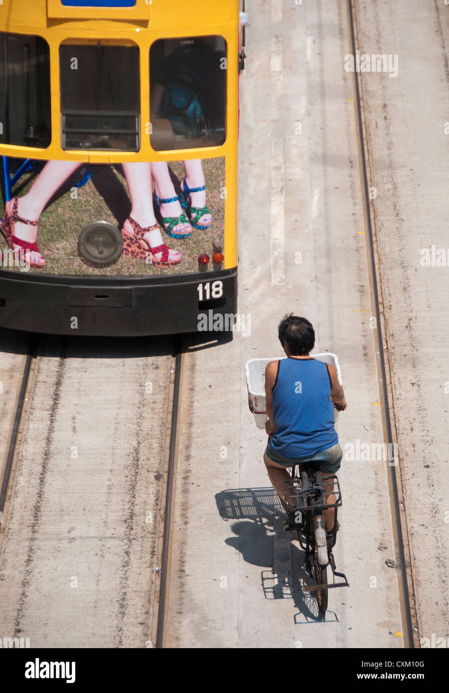 Bicycle delivery man following a tram along Hennessey Road, Hong Kong - Stock Image