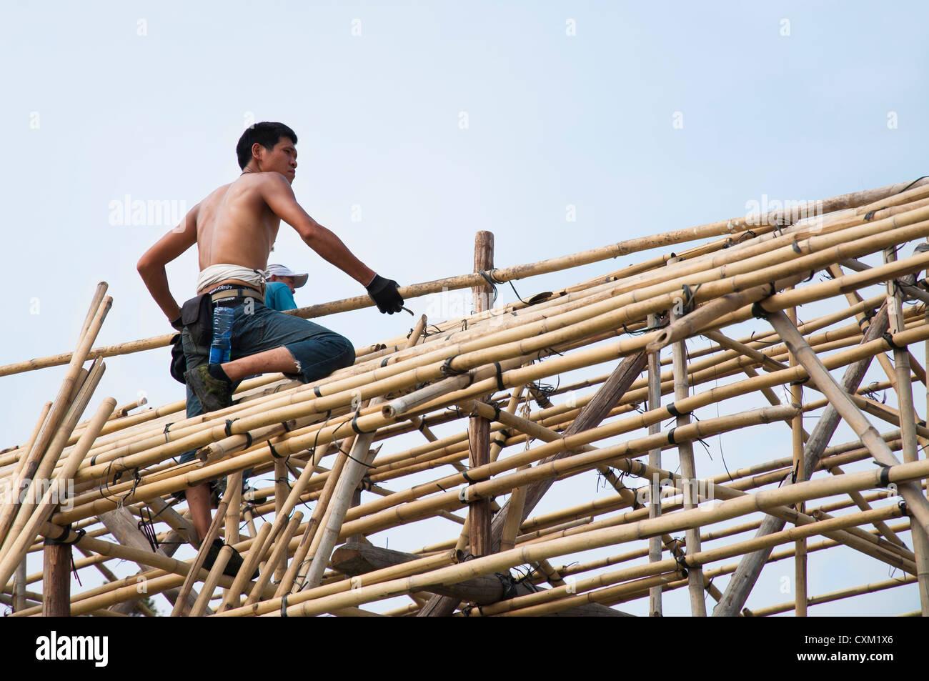 Workman erecting bamboo scaffolding before the Cheung Chau bun festival, Hong Kong - Stock Image