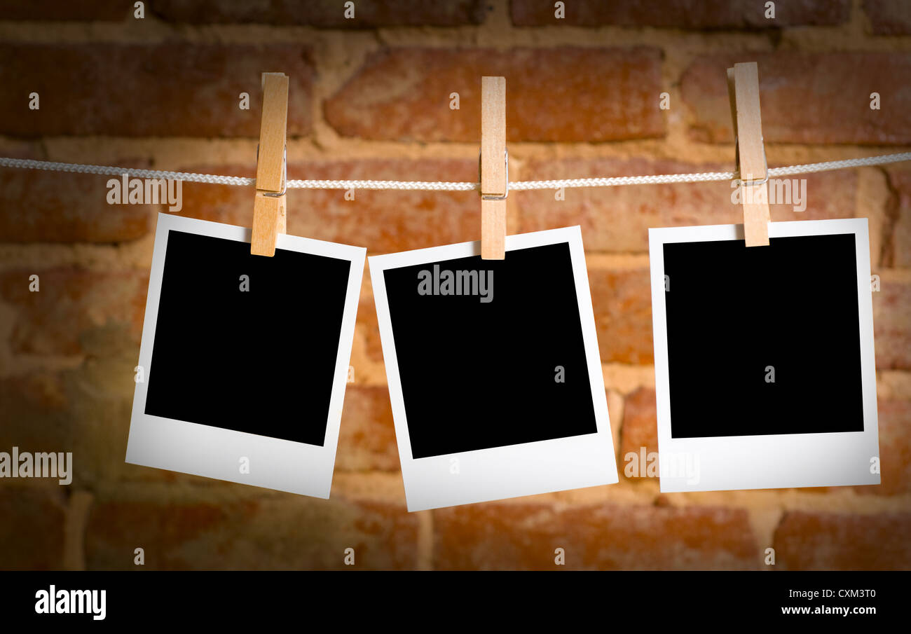 instant transfer pictures on a rope with clothespins, with clipping path for images, in front of a brick wall - Stock Image