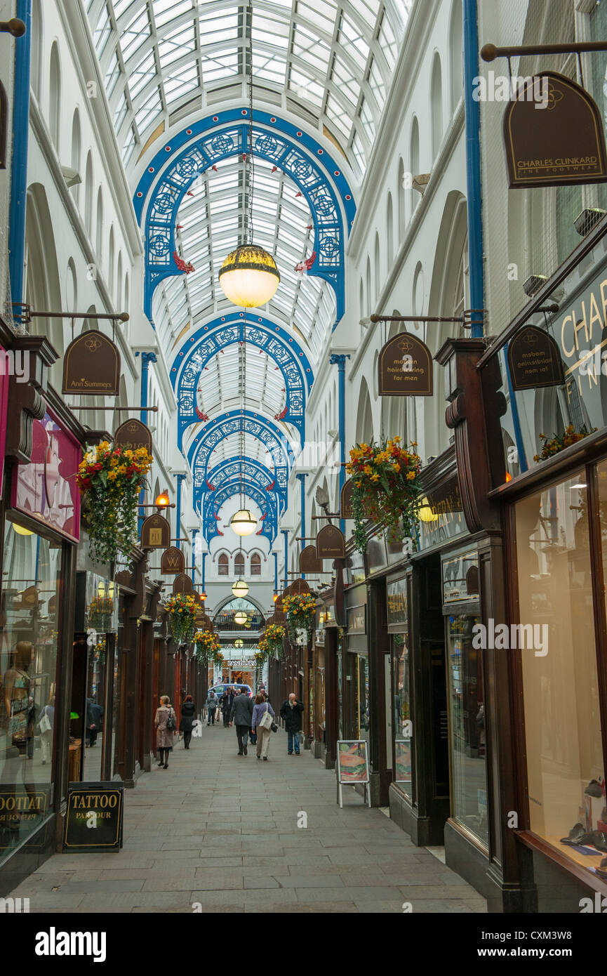 Shoppers walking down historic Thornton's Arcade (rows of shops under impressive glass arched roof) - Leeds - Stock Image