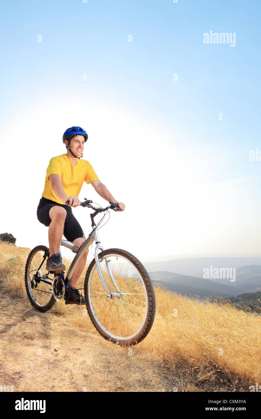 A view of a young biker riding a mountain bike on a sunset, Macedonia - Stock Image