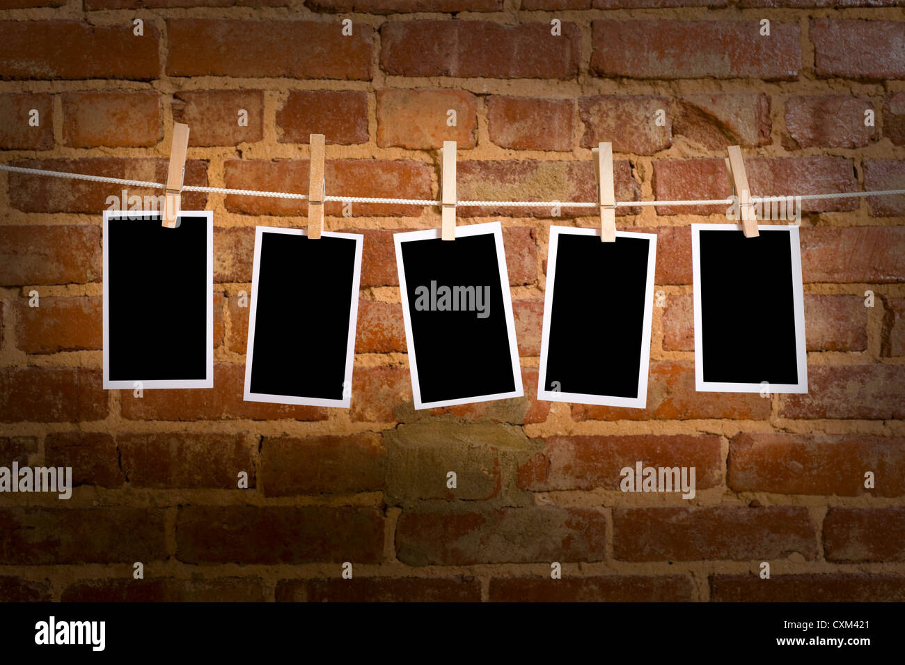 pictures or photographs on a rope with clothespins, with clipping path for images, in front of a brick wall - Stock Image
