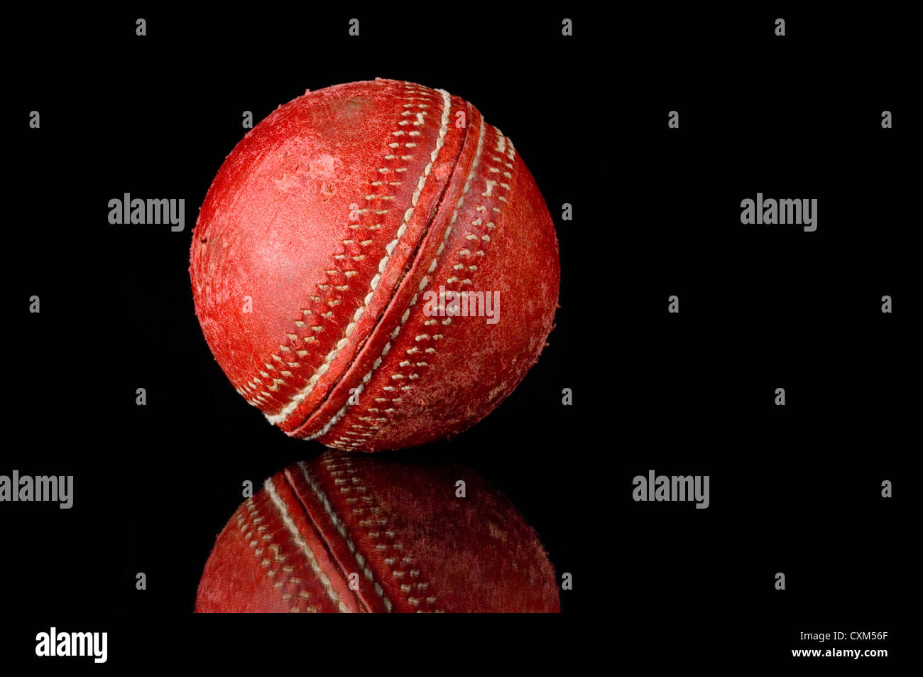 Red, scuffed Cricket ball on black background with reflection - Stock Image