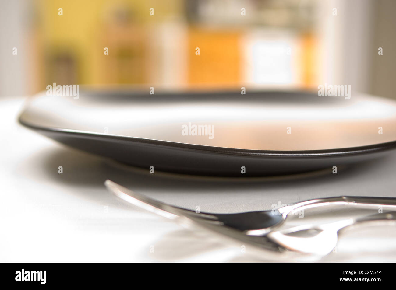 Dinnerware setting with black plates and flatware - Stock Image