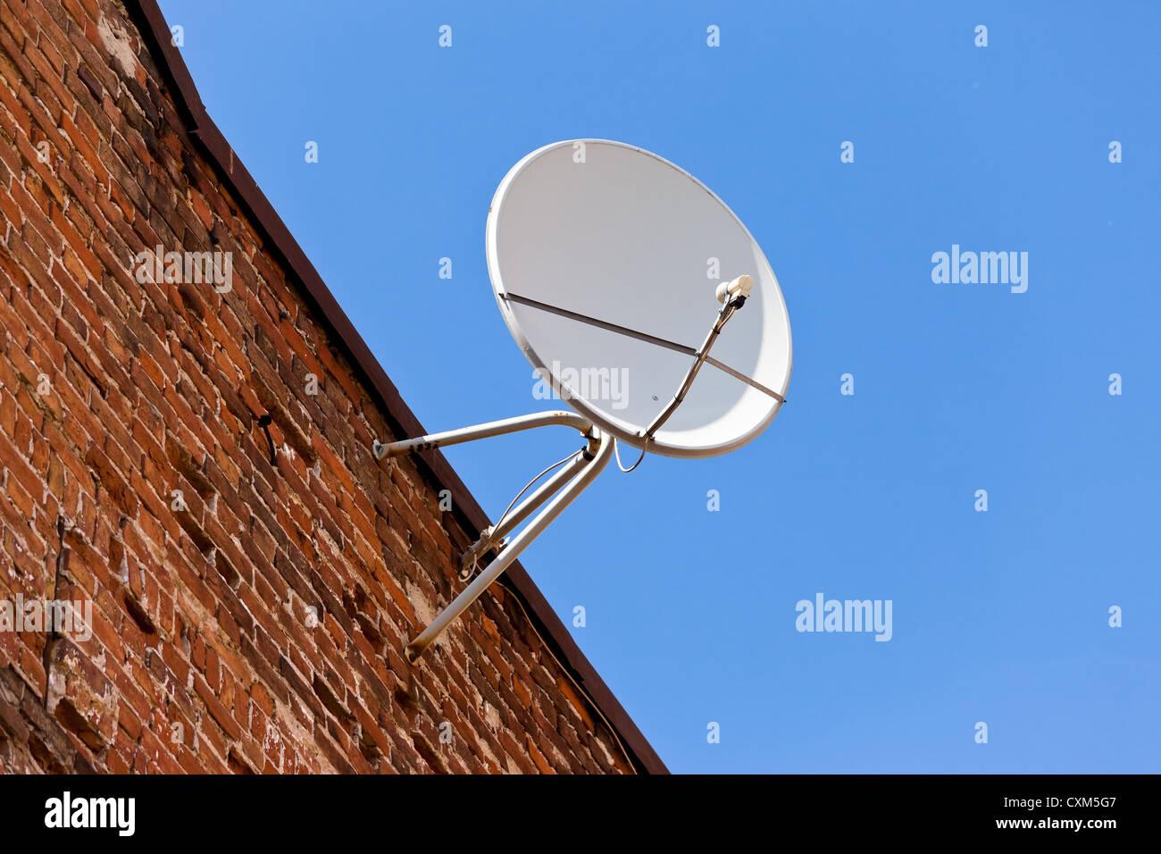 Satellite Dish mounted on old brick wall. Stock Photo