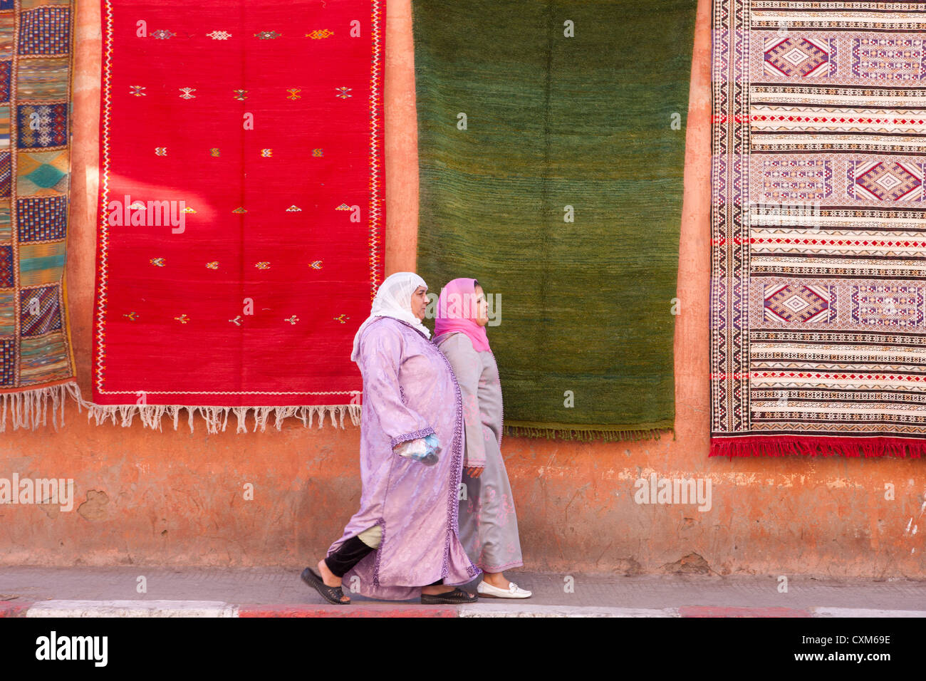 Two women walking along pavement with carpets hanging on wall behind them, Marrakech, Morocco - Stock Image
