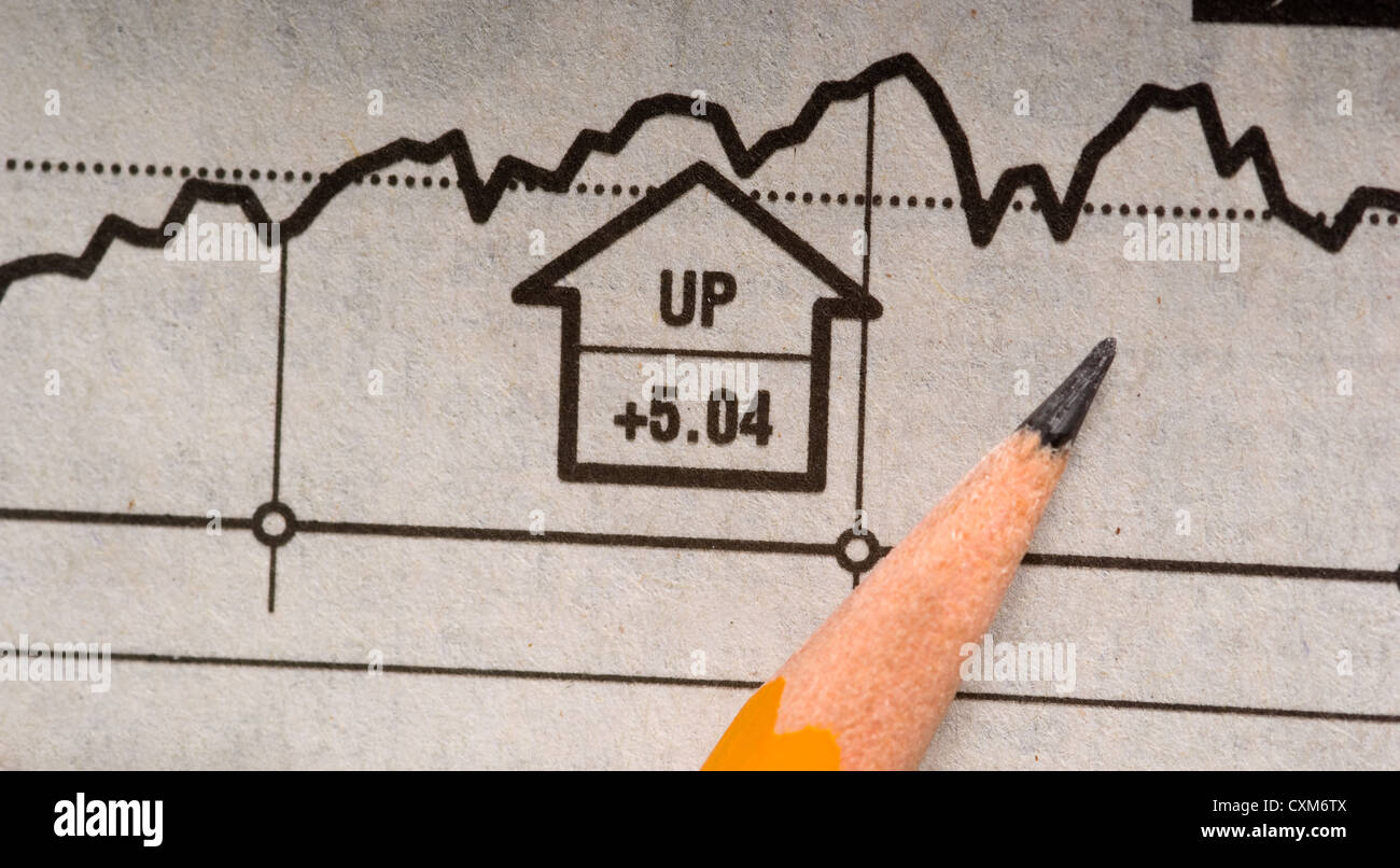 A pencil lying on top of a newspaper stock chart signaling an increase in price or a rising market - Stock Image
