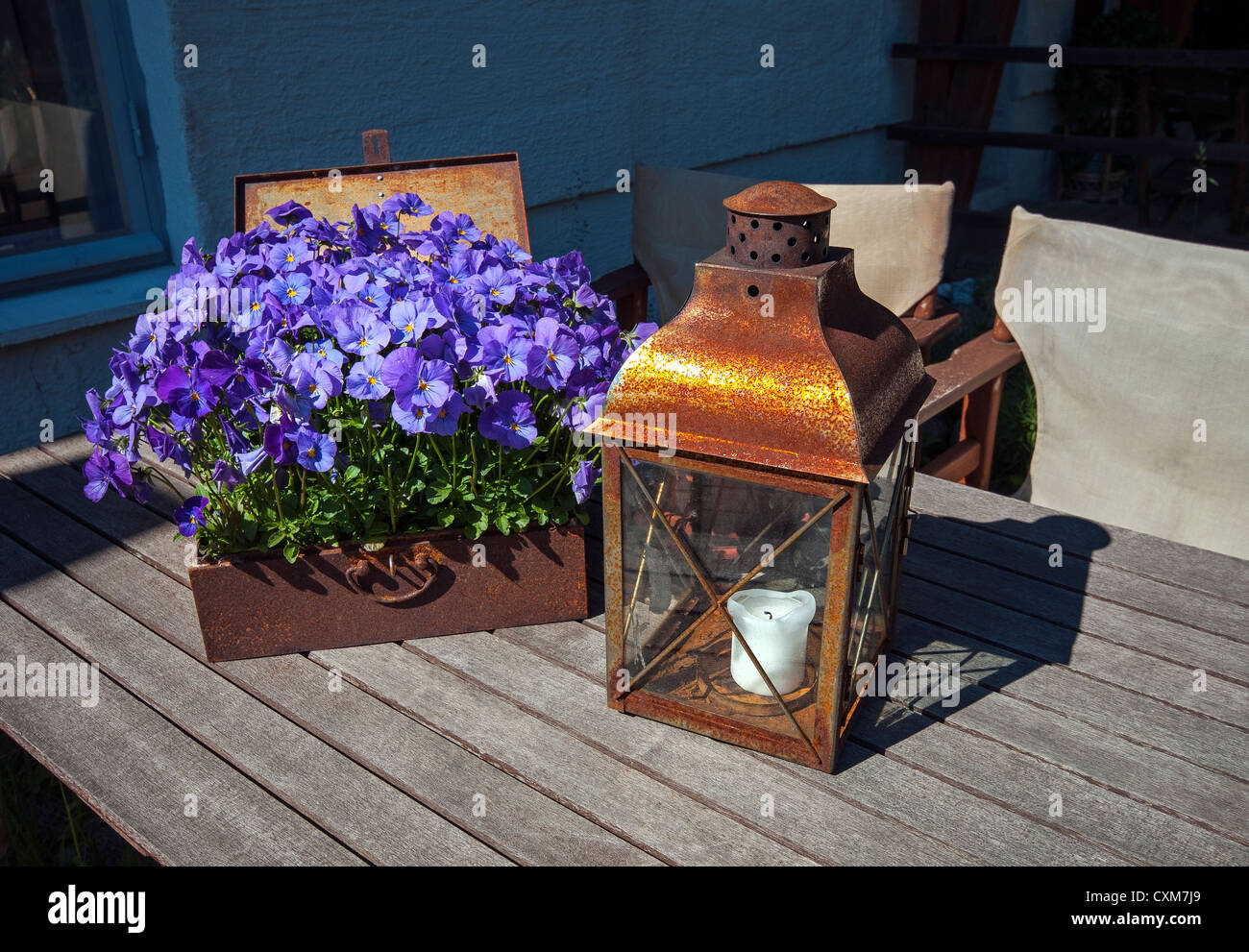 Rusty chest with purple flowers and lamp on wooden table in 'Old Town' Helsinki, Finland Stock Photo