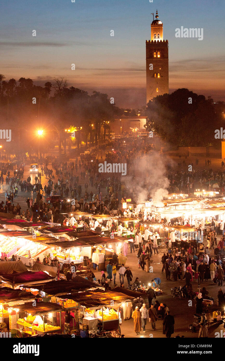 Market stalls and people at dusk in Fna Jamaa el Fna Square with Souk Koutoubia Minaret Mosque Stock Photo