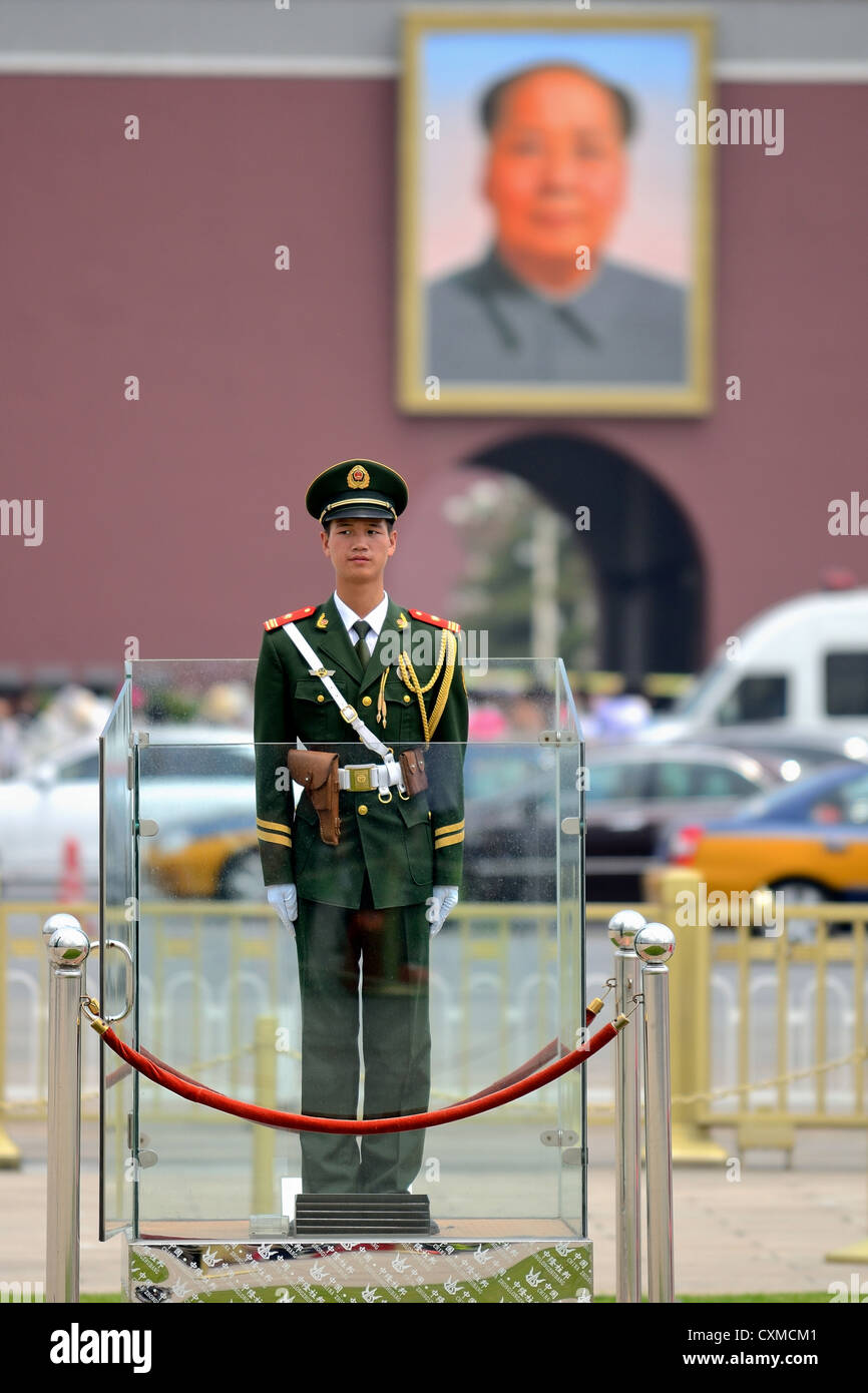 Guard standing at attention in Tiananmen Square with large portrait of Mao in background. - Stock Image