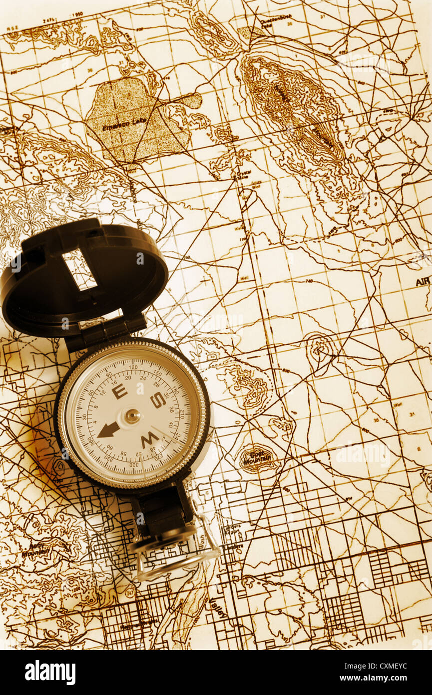 A compass lying on top of a topographical map - Stock Image