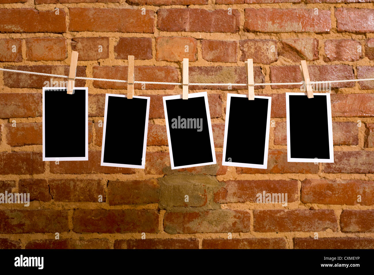 pictures on a rope with clothespins, with clipping path for images, in front of a brick wall - Stock Image