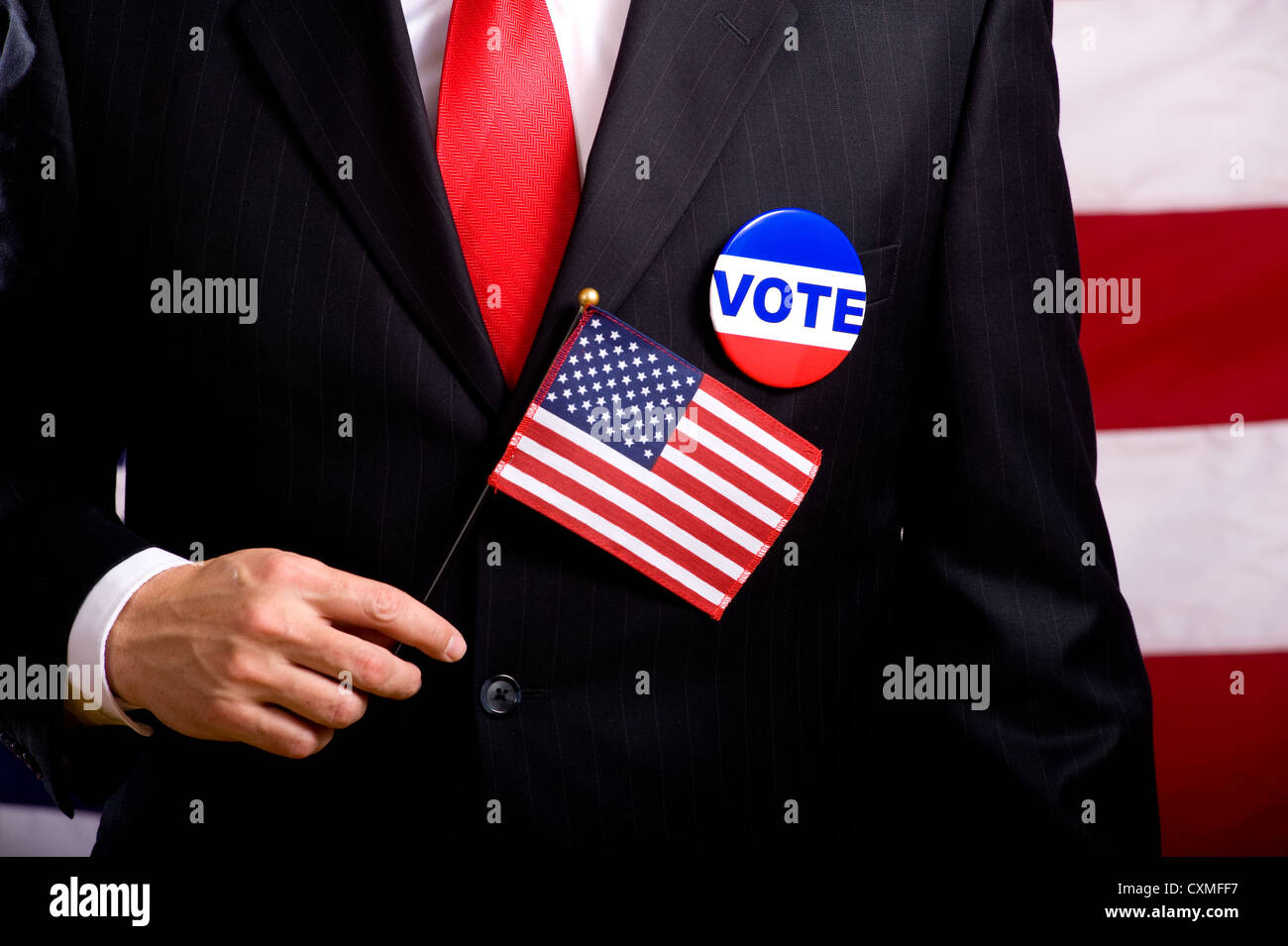 A man wearing a blue business suit and tie with a vote button and US flag. Election day background or concept Stock Photo