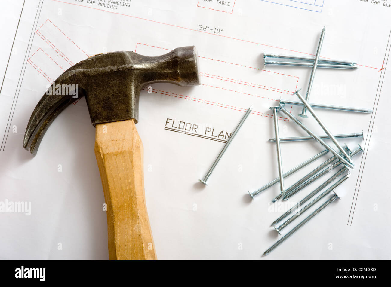 The House Of Hammer a hammer and nails lying on top of a house floor plan or