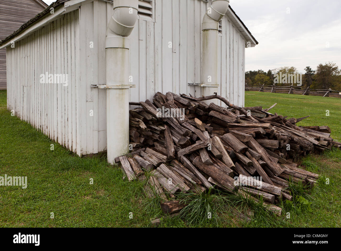 Firewood pile in the back of shed - Stock Image