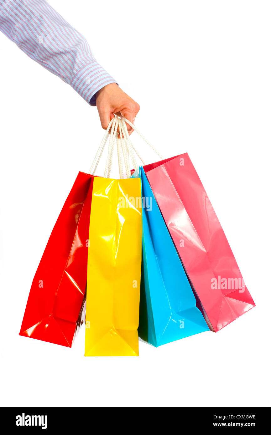 A ladies hand gripping several brightly colored shopping bags on a white background - Stock Image