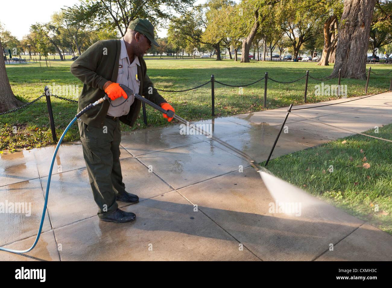 Municipal worker pressure washing sidewalk - Washington, DC USA - Stock Image