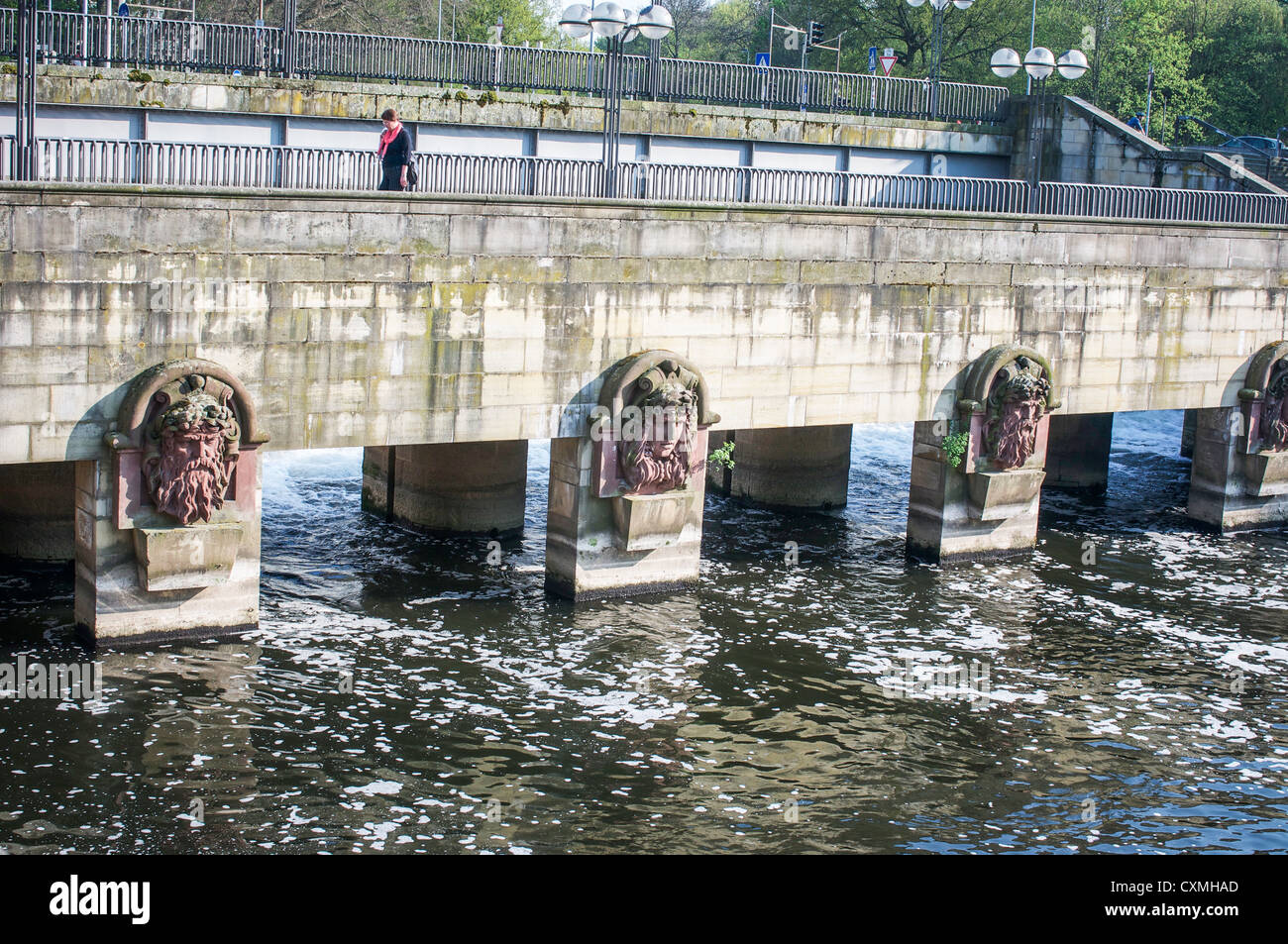 Woman walks over a pedestrian bridge across the water in Hannover, Germany with sculpted river god heads on support - Stock Image