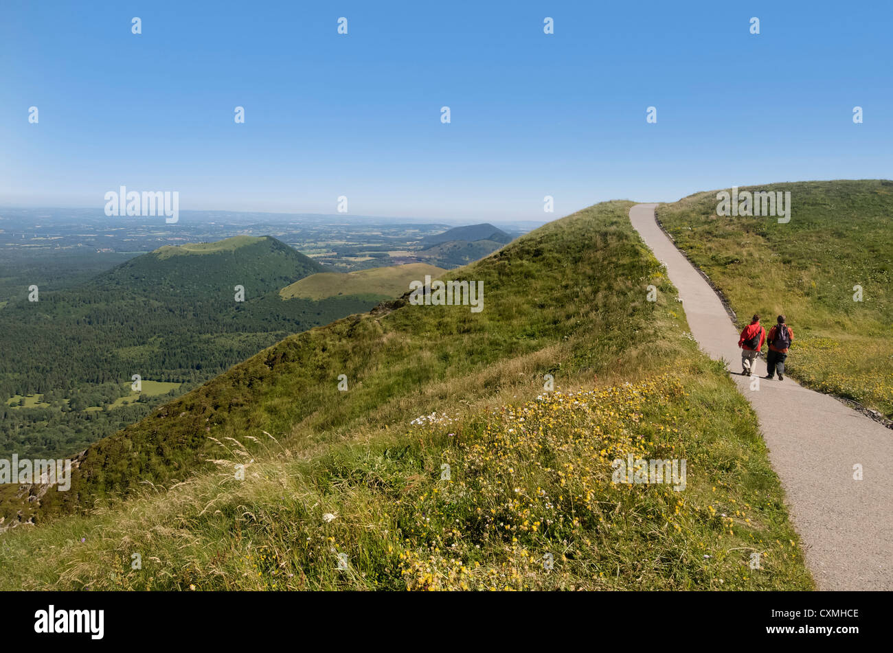 Hikers and view from Puy de Dome onto the volcanic landscape of the Chaine des Puys, Massif Central, Auvergne, France, - Stock Image