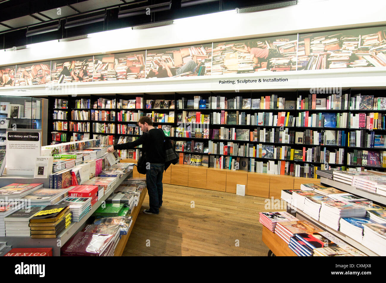 Man browsing through the art and design books for sale in a large shop in London, England. - Stock Image