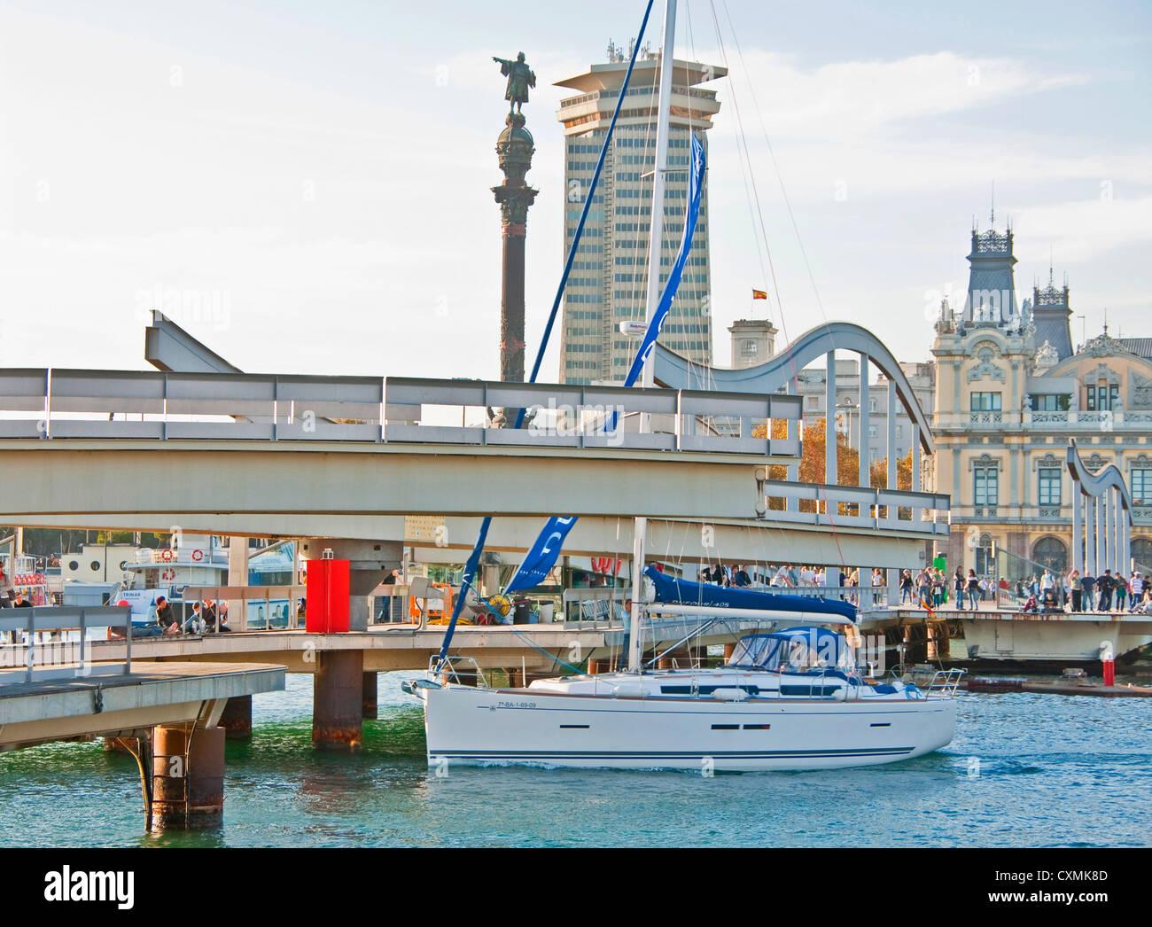 Rambla del Mar pedestrian bridge at Barcelona's Port Vell opening for sailboat to leave Darsena Nacional marina - Stock Image