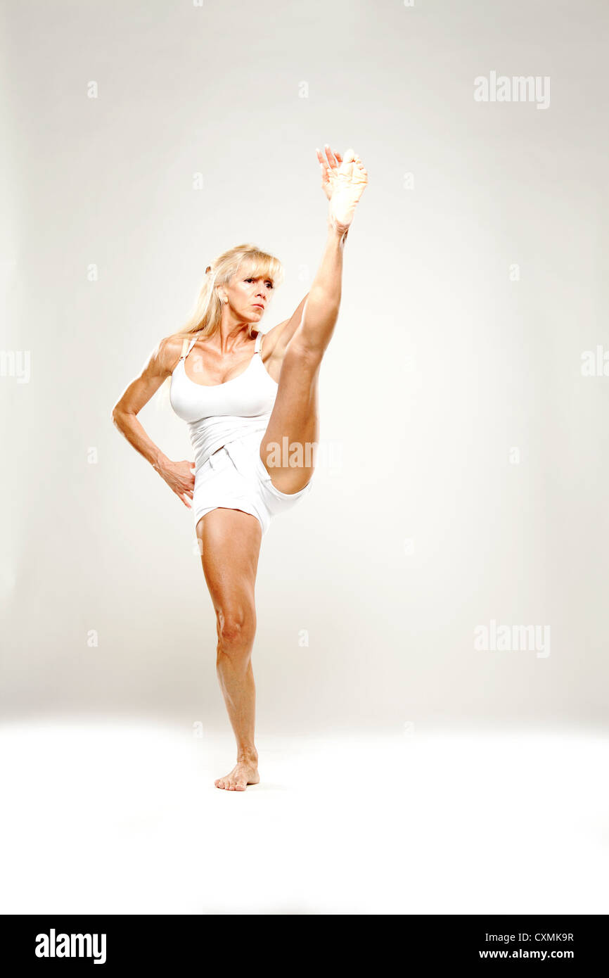 Mature woman dancing and stetching in studio - Stock Image