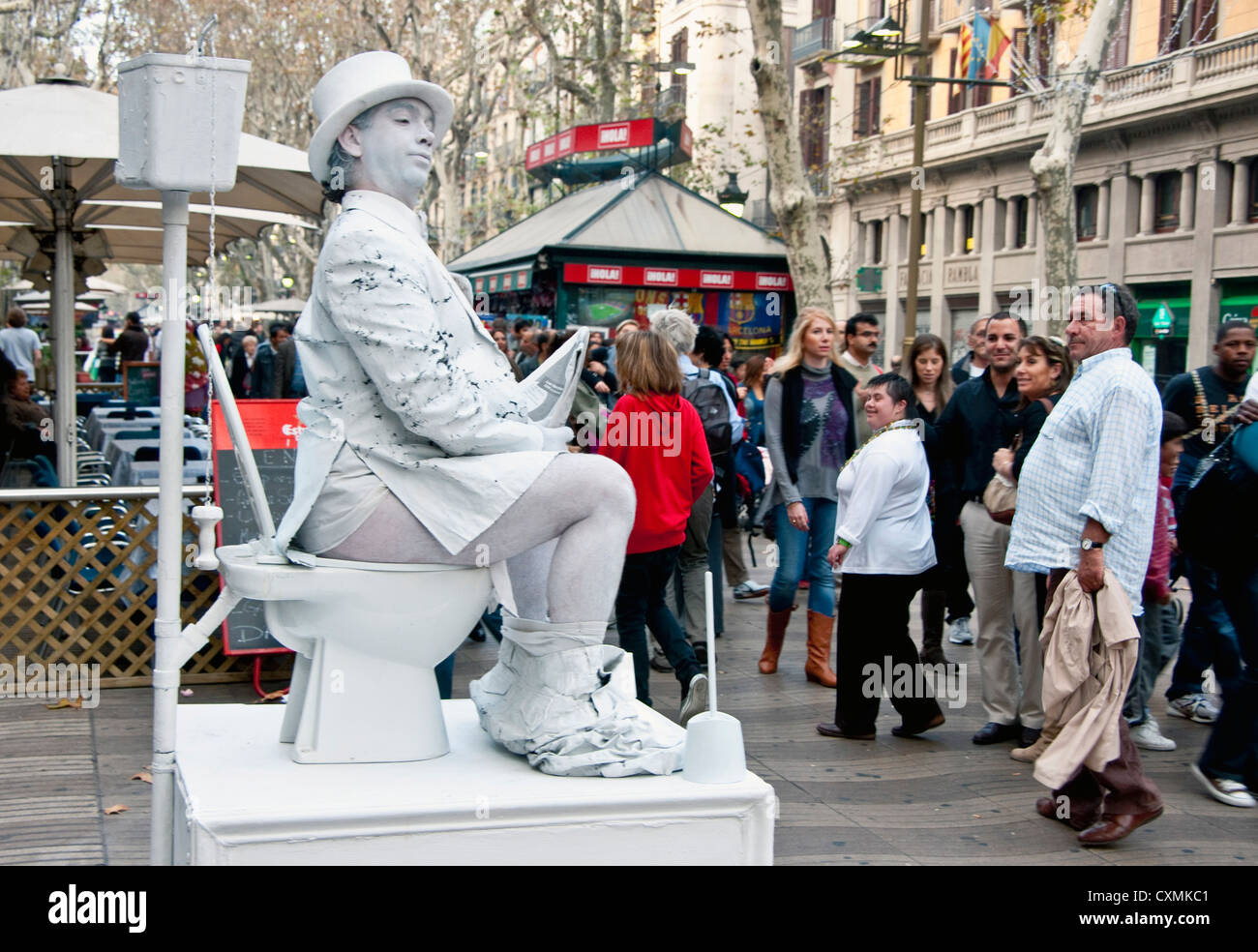 Mime on Las Ramblas in Barcelona sitting on toilet reading newspaper - Stock Image