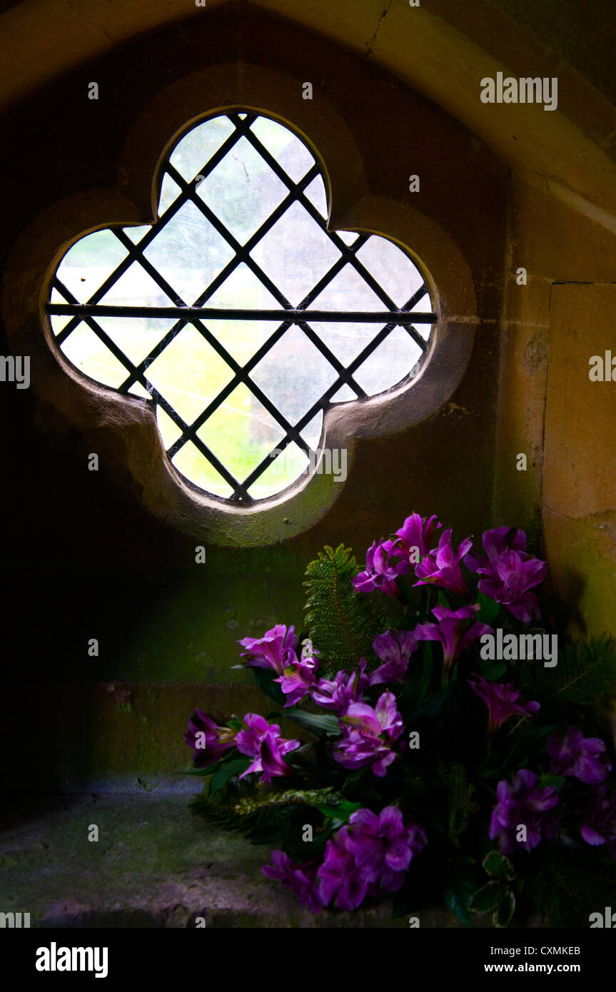 An ornate, leaded cross-shaped window in the porch of a church, decorated with a bouquet of purple flowers. - Stock Image