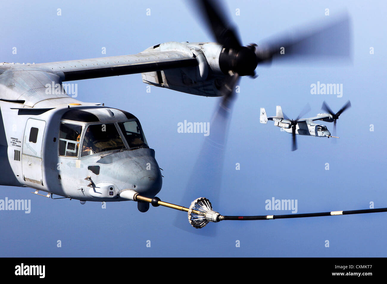 A US Marine MV-22B Osprey connects to the refueling hose of a KC-130J Hercules during aerial refueling September - Stock Image