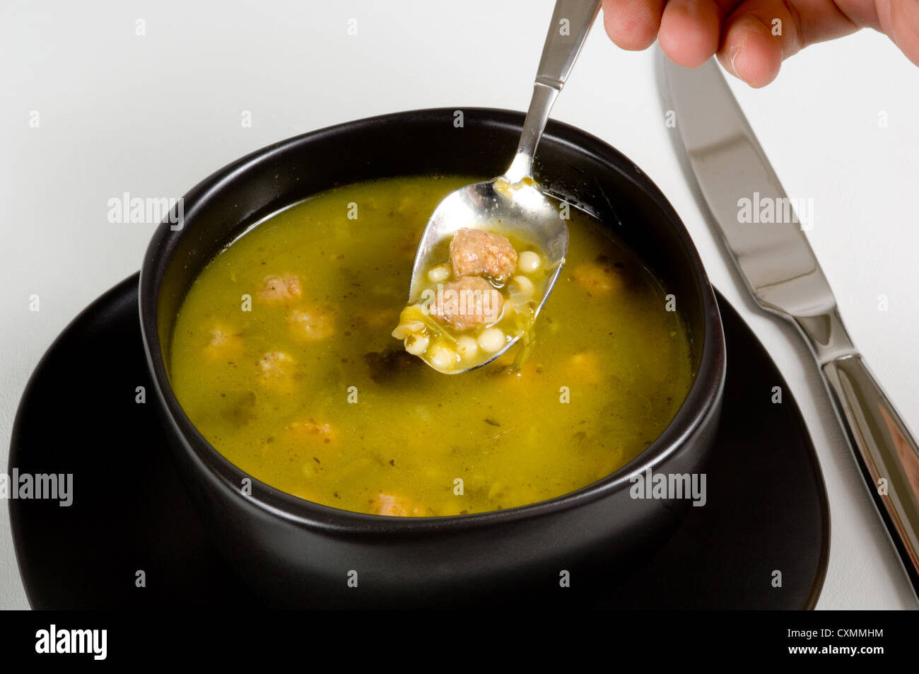 Bowl of Italian Wedding soup on white in black bowl with flatware - Stock Image