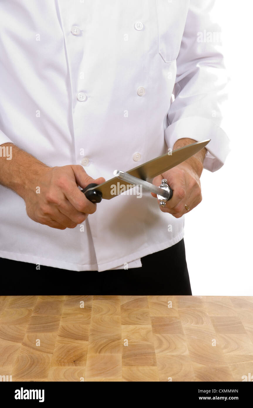 Professional chef (man) sharpening knife with steel - Stock Image