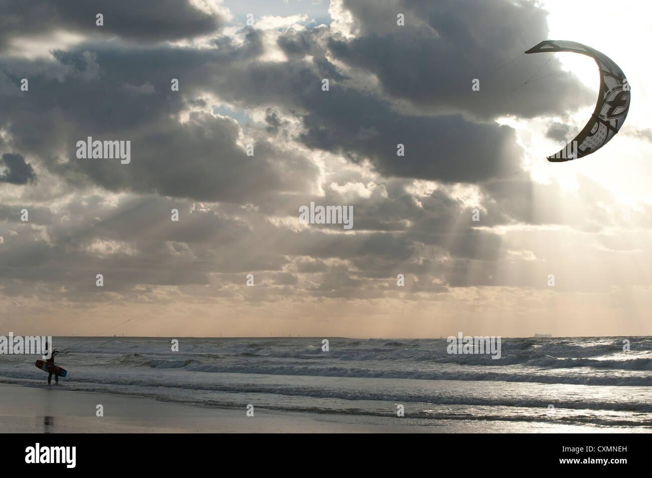 kitesurfer on beach at sunset - Stock Image