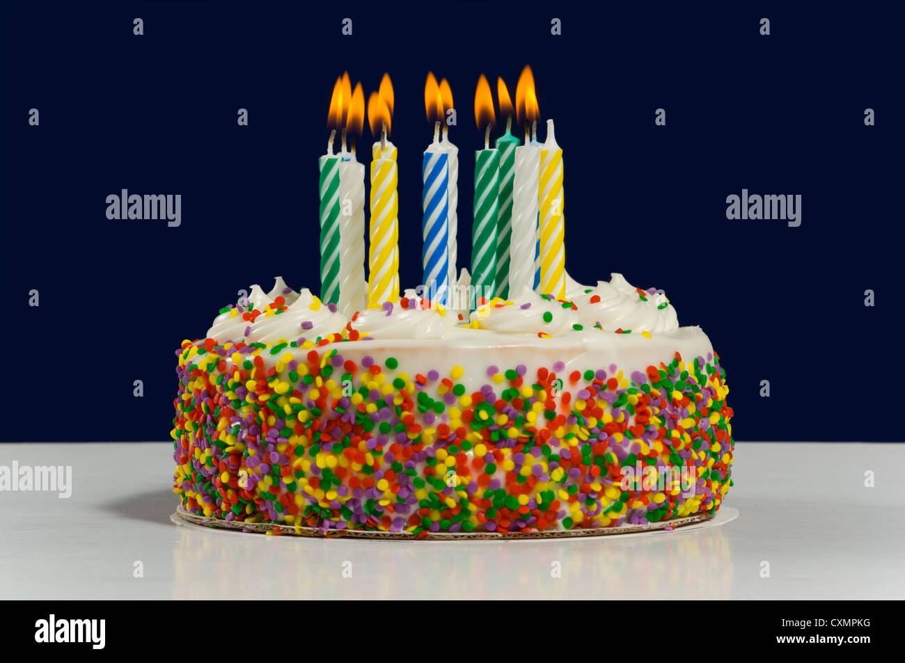 White Birthday Cake With Candy Sprinkles Multi Colored Candles On Dark Blue Background