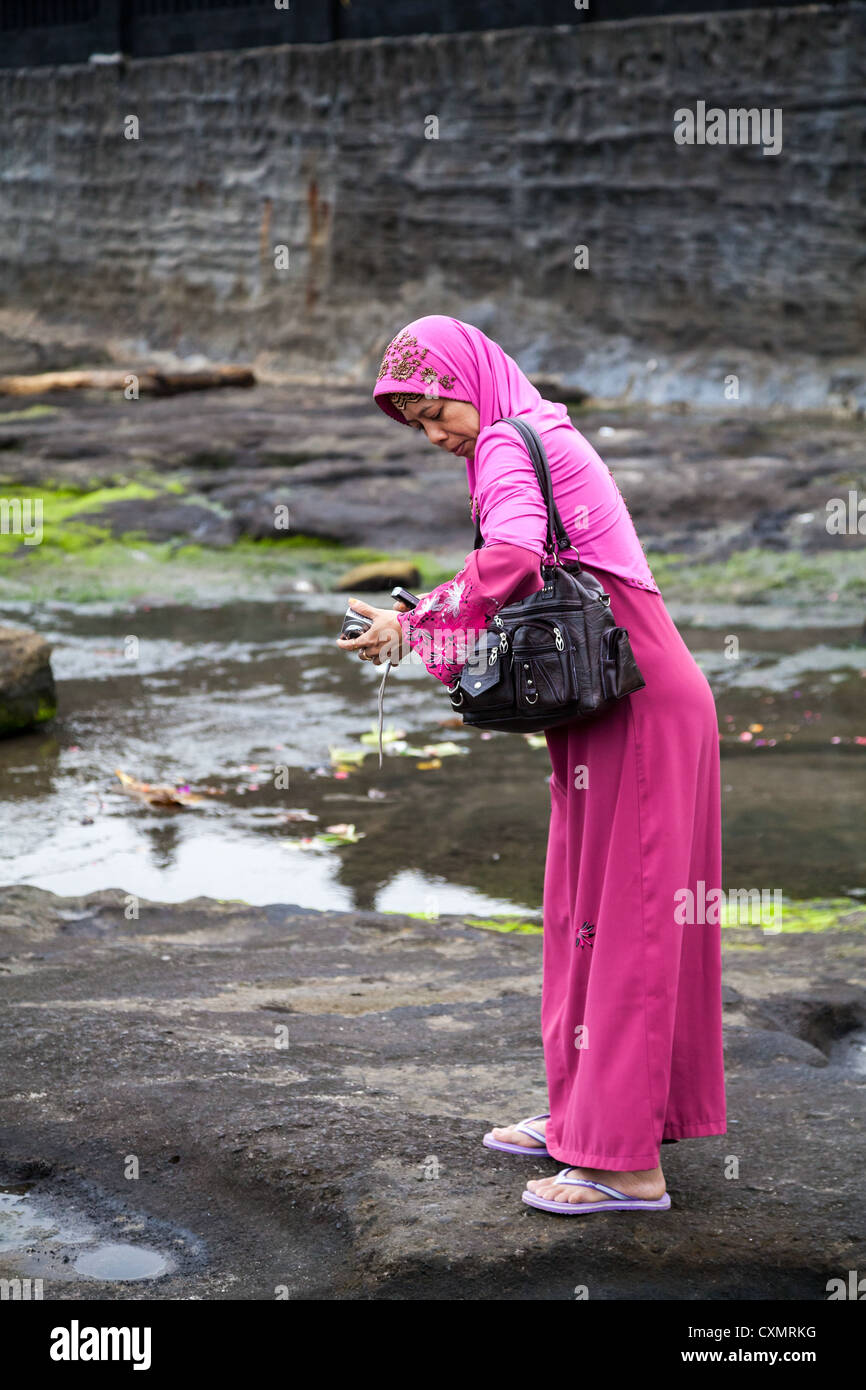 Woman on the Beach at the Temple Pura Tanahlot on Bali Stock Photo