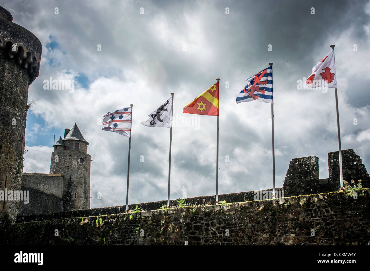 Flags fluttering in a strong breeze atop the stone walls of medieval fortified Chateau de Fougeres in Brittany, - Stock Image