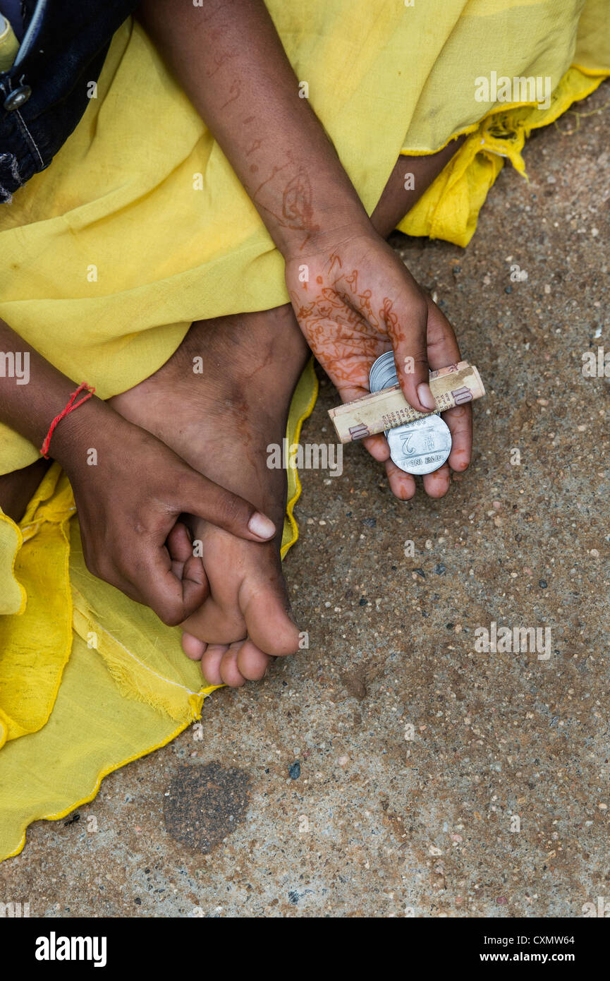 Indian street girl begging for money with rupee coins in her hand. Andhra Pradesh, India - Stock Image