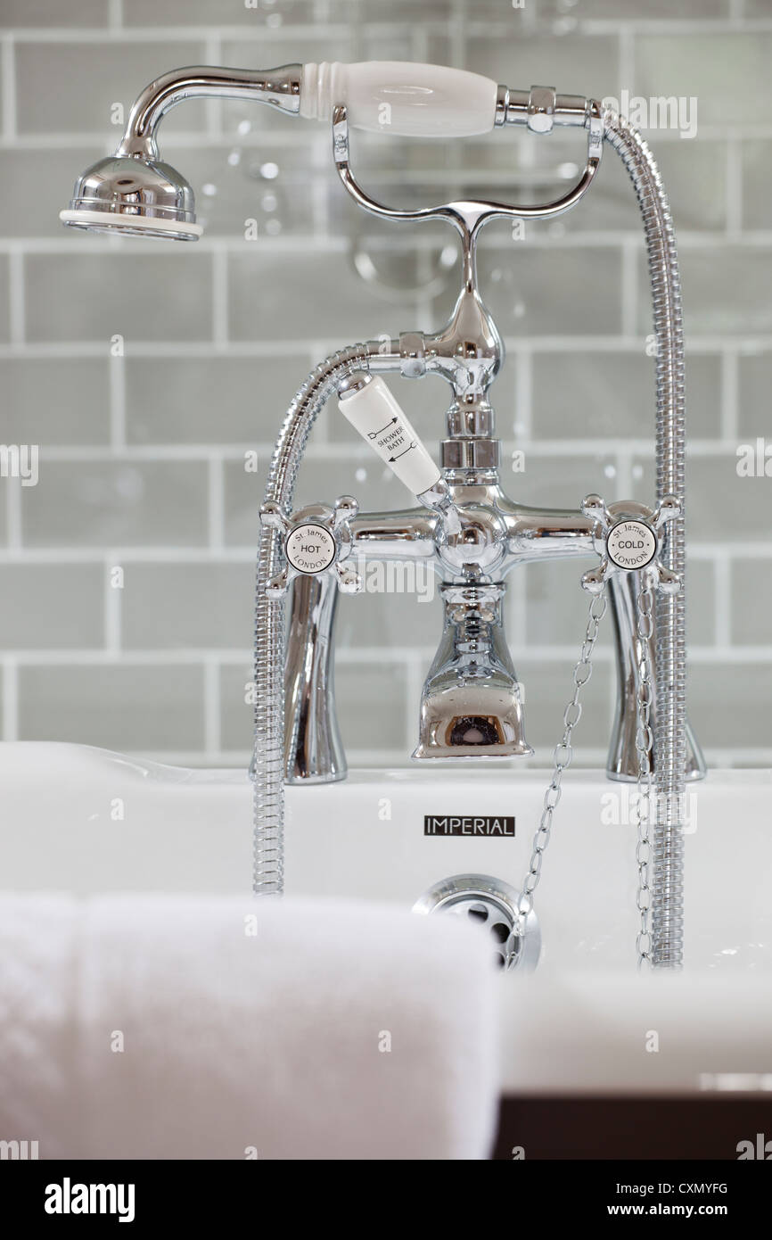 Modern mixer taps over bath with tiled wall behind - Stock Image