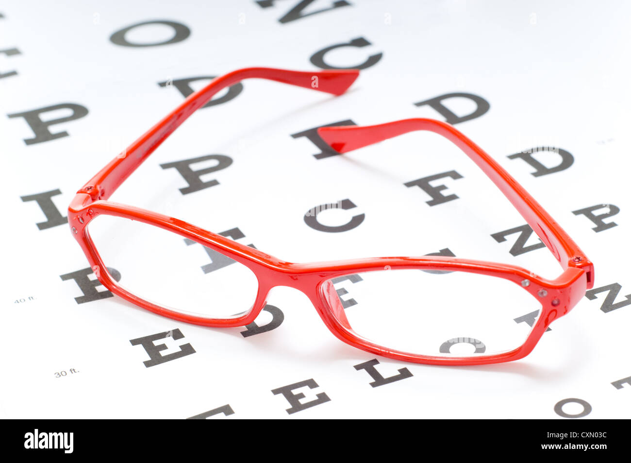 A Pair Of Red Reading Glasses Or Spectacles On An Snellen Eye Chart