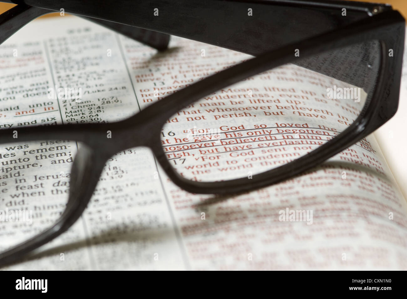 A pair of reading glasses on top of a a Bible open to John 3, religious study Stock Photo