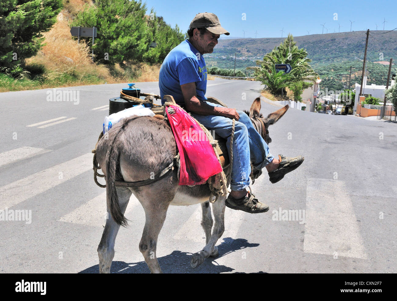 Man travelling on a donkey  as means of his transport on a  hlll top road near Sitia  Crete Greece - Stock Image