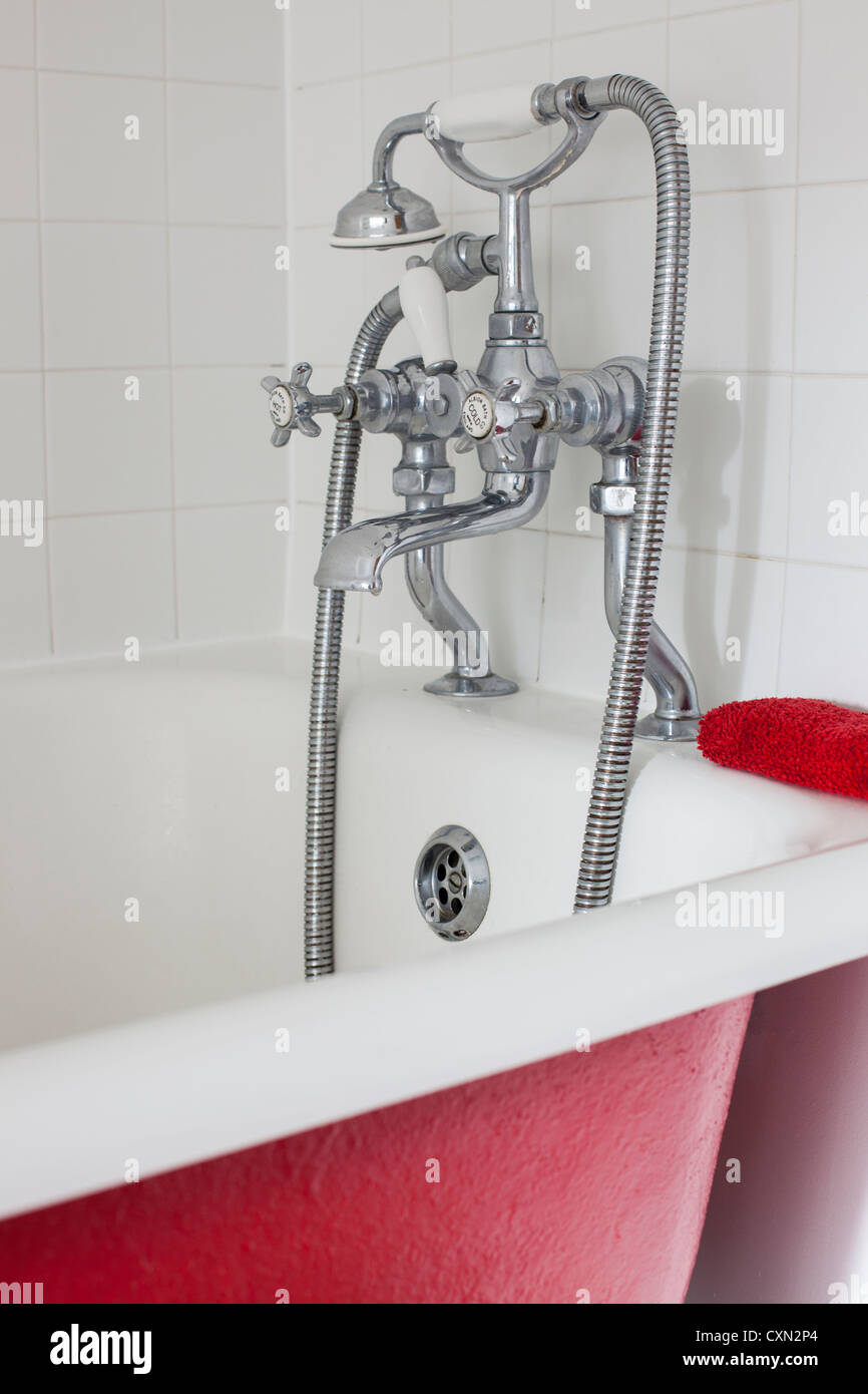 Red painted roll-top bath with mixer taps - Stock Image