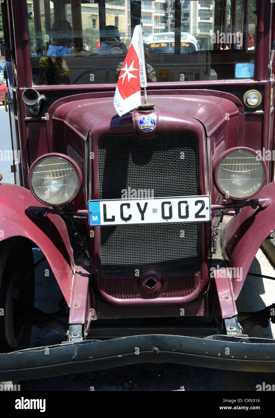 Vintage bus Maltese flag front view Bedford headlamps radiator - Stock Image